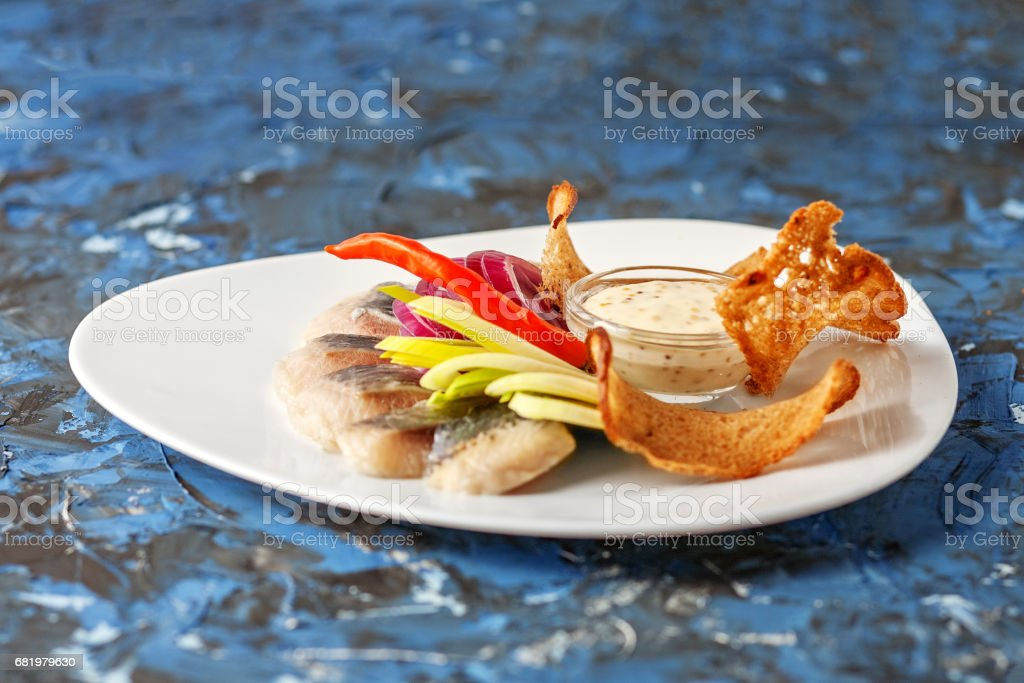 Dish with herring and bread chips on a blue background. The concept of food, restaurant, banquet. stock photo