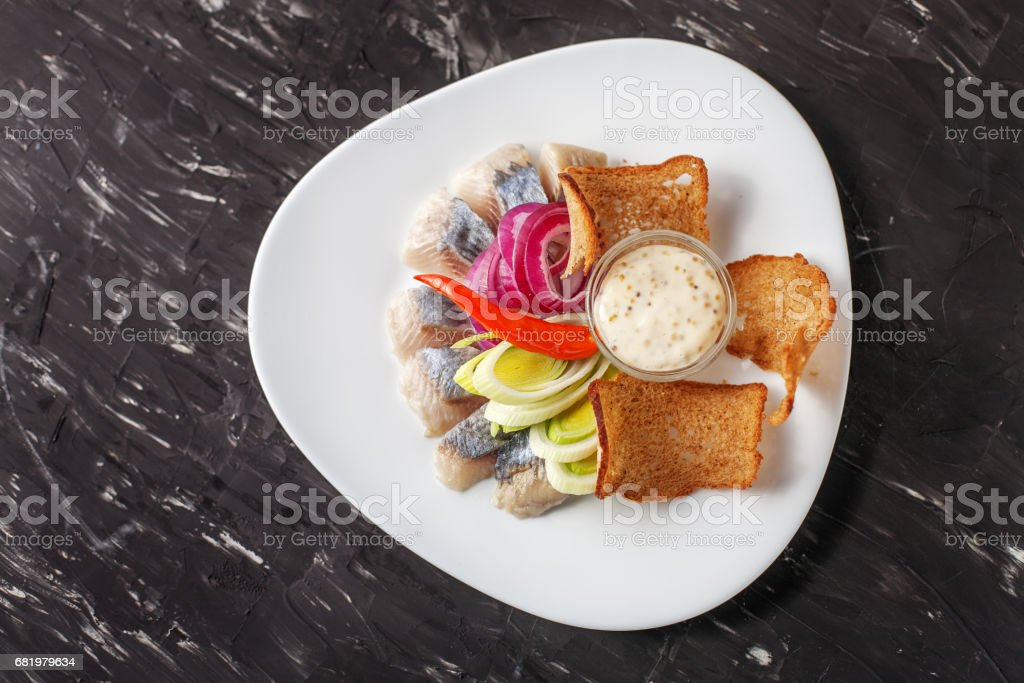 Dish with herring and bread chips. Top view. The concept of food, restaurant, banquet. stock photo