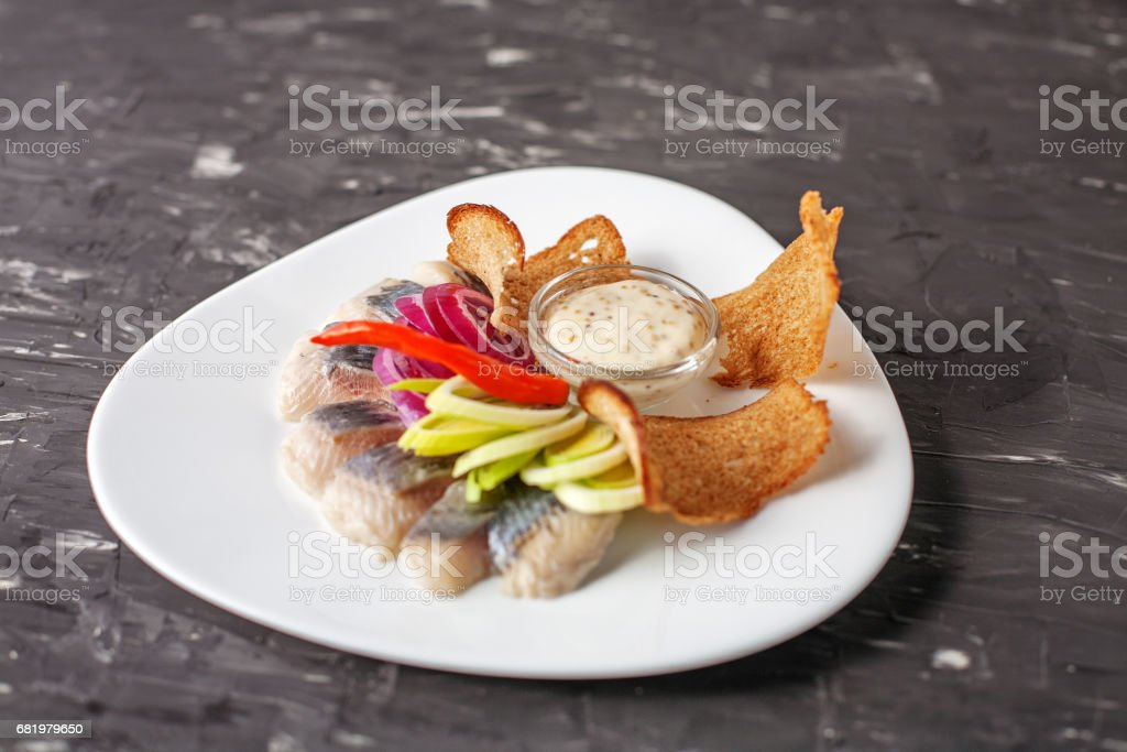 Dish with herring on a white plate. The concept of food, restaurant, banquet. stock photo
