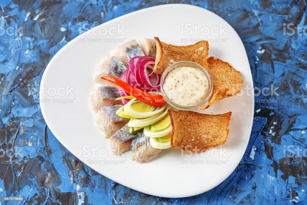 Dish with herring on a white plate. Top view. The concept of food, restaurant, banquet. stock photo