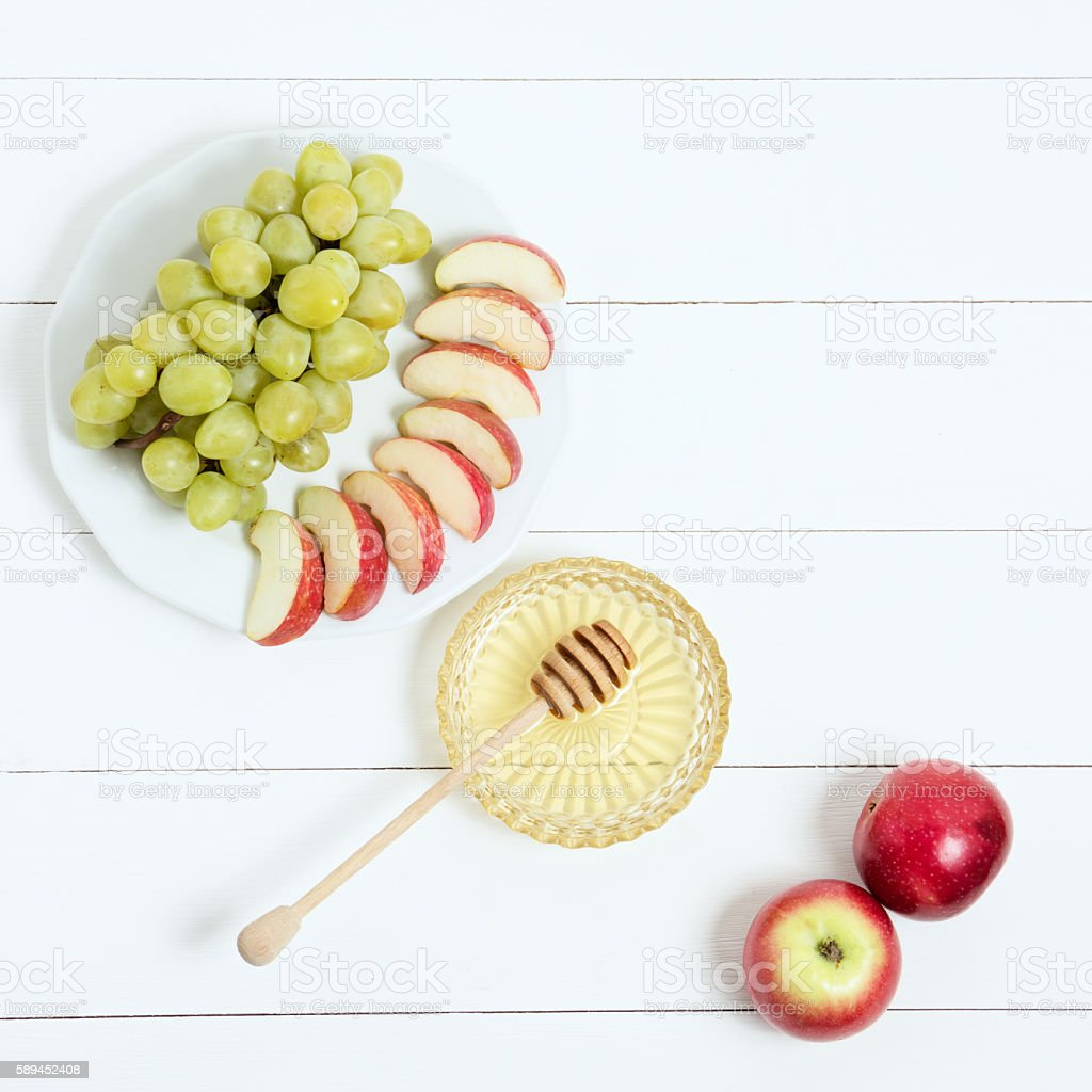 Dish with honey, fruit and apples on white wooden background stock photo