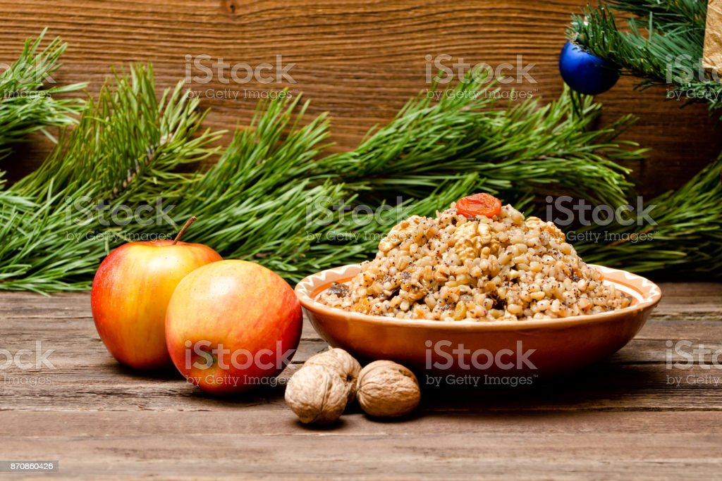 Dish with kutia. Traditional Christmas treat of the Slavs on Christmas Eve. Fur-tree branch and  apples on a wooden background. stock photo