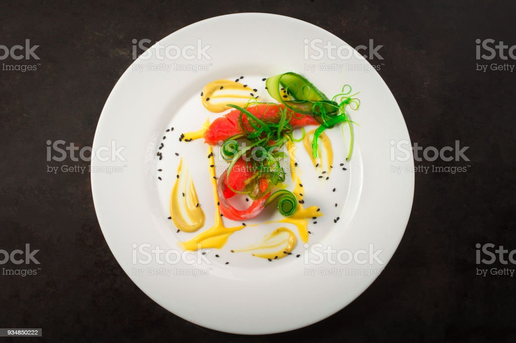 Dish with salmon, seaweed and cucumber. Old black rustic background. Top view stock photo