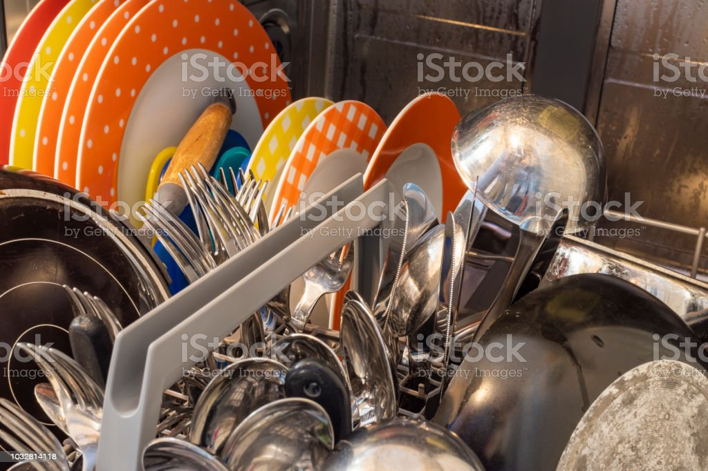 Dishes and cutlery in a dishwasher after the wash.