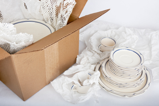 Studio shot of dishes being wrapped in tissue paper and packed in a cardboard box.