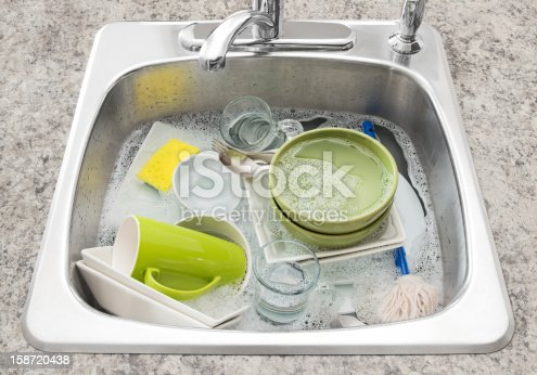 Dishwashing. Bright dishes soaking in the kitchen sink.