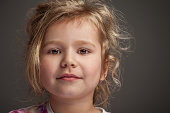 Disheveled cute little girl on grey background. This file is cleaned and retouched.