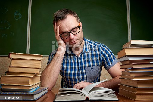 926239360 istock photo A disheveled tired unshaven young man with glasses holds his head and reads a book at the table with piles of books against the background of a blackboard. 1128404831