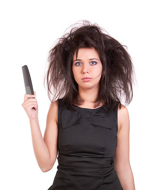 disheveled woman holding a comb - messy hair stock photos and pictures