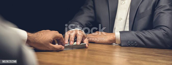 istock Dishonest businessman secretly giving money to his partner in the dark 952625298