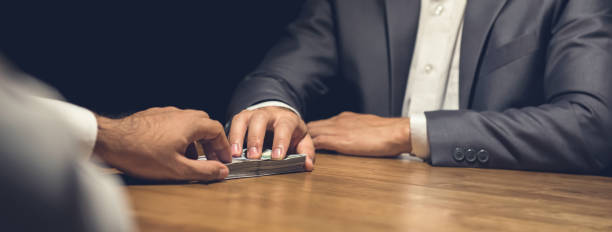 Dishonest businessman secretly giving money to his partner in the dark Dishonest businessman secretly giving money to his partner in the dark - bribery and venality concepts, panoramic web banner borrowing stock pictures, royalty-free photos & images