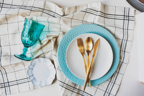 dishware winter set in blue and white tones with gold cutlery on white background. Plates, wine glass on table stock photo