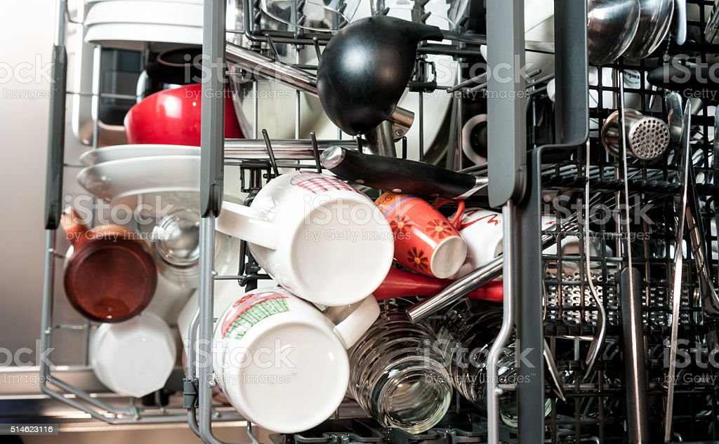 Dishwasher rack full of plates, stoves and cups rack stock photo