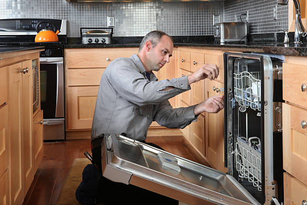 Dishwasher Repair Worker repairing energy efficient dishwasher in beautiful, contemporary kitchen. dishwasher stock pictures, royalty-free photos & images