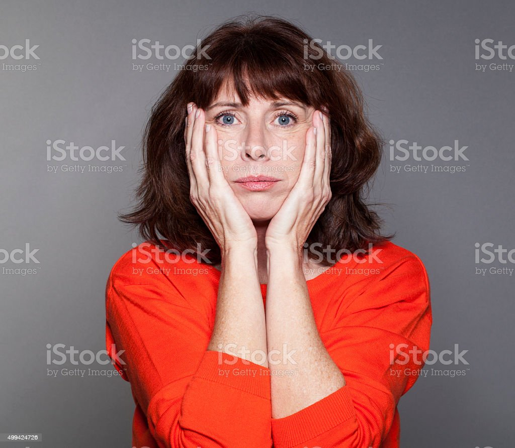 disillusioned mature woman expressing regret and sadness with her face stock photo