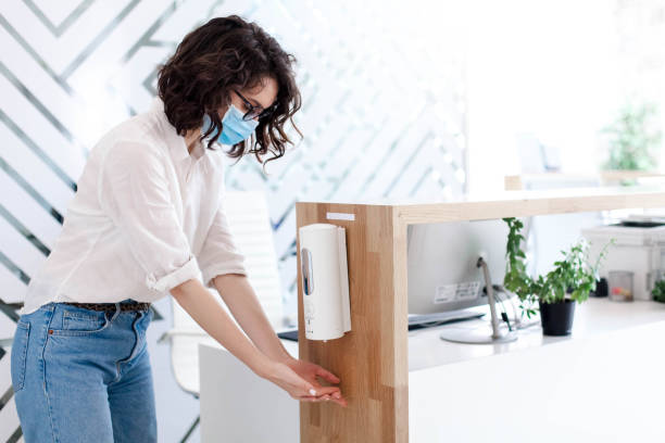 Disinfectant liquid in office. Disinfection hands with sanitizer in public place. Hygiene, staff safety. stock photo
