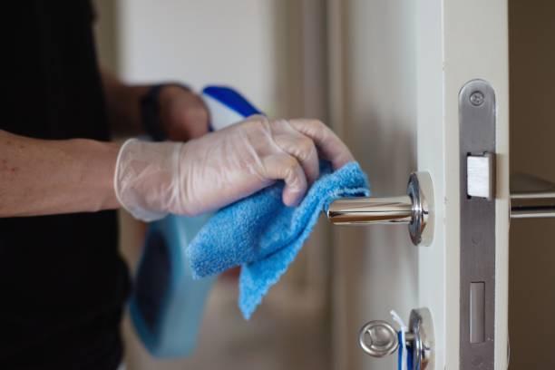 Disinfecting a door knob stock photo