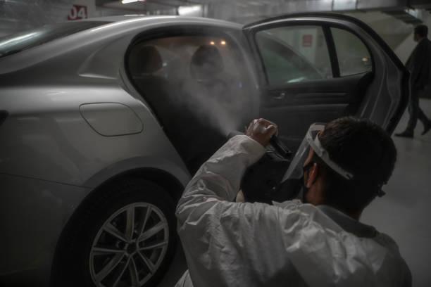 desinfektionsbemühungen von fahrzeugen im rahmen der bekämpfung des covid-19-virus - auto trennwand stock-fotos und bilder