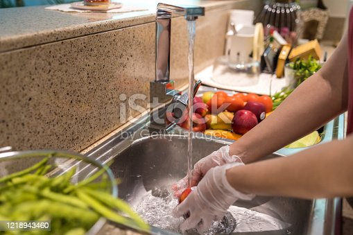 COVID-19, Coronavirus, Precaution, Part of a Series - Woman wearing gloves cleaning the fresh fruits in the kitchen sink