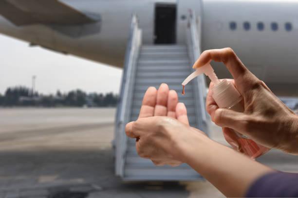 Hände desinfizieren, bevor man ins Flugzeug steigt – Foto