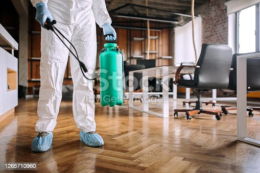 Man in protective suit spraying for disinfection in the office
