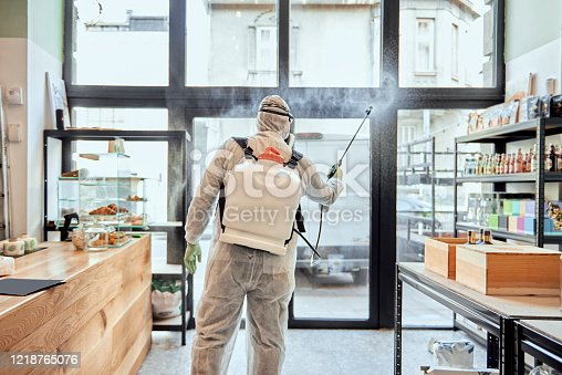 Man in protective suit disinfecting and spraying shop interior