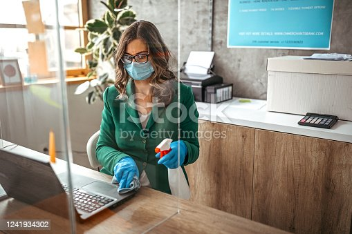 Businesswoman with surgical gloves cleans and disinfects his table in the office. Office with acrylic glass partition on desk. Acrylic glass wall - protection against coughs and spitting, protection against viruses.