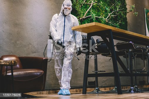 Man in protective suit spraying with disinfectant bar, cafe and restaurant interiors to prevent further spread of the coronavirus
