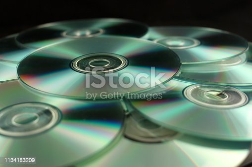 Many compact disks CD on pile against black background.