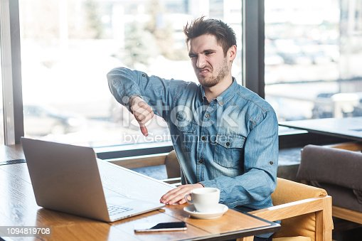 Dislike! Side view portrait of negative critique bearded young freelancer in blue jeans shirt are sitting in cafe and making video call on laptop and showing thumb down to his companion. indoor,inside