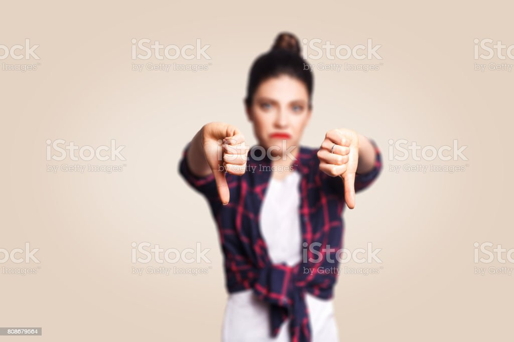 Dislike. Young unhappy upset girl with casual style and bun hair thumbs down her finger stock photo