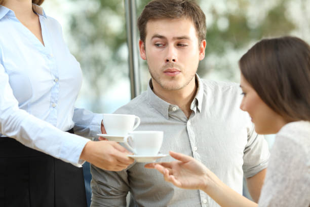 disloyal boyfriend looking at breast of a waiter - boyfriend stock photos and pictures