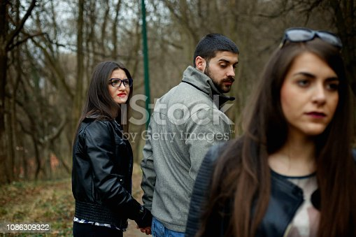 istock Disloyal man walking with his girlfriend and looking amazed at another seductive girl 1086309322