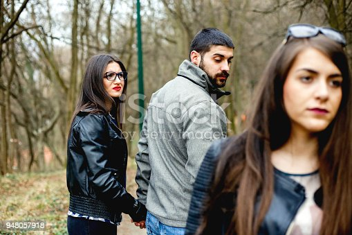 468456828istockphoto Disloyal man walking with his girlfriend and looking amazed at another seductive girl 948057918