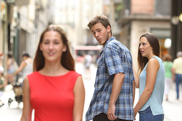 Disloyal man with his girlfriend looking at another girl Disloyal man walking with his girlfriend and looking amazed at another seductive girl husband stock pictures, royalty-free photos & images