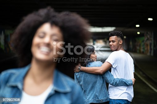 istock Disloyal man with his girlfriend looking at another girl 972902508