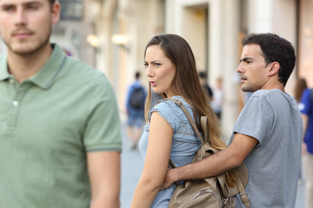 Disloyal woman looking another man and her angry boyfriend stock photo