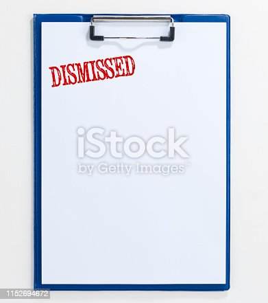 "looking down on a notepad quoting ""Dismissed"" written with rubber stamp"