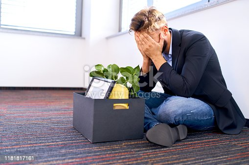istock Dismissed millenial sitting on the office floor 1181817161