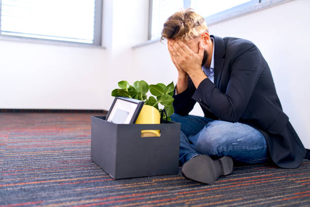Dismissed millenial sitting on the office floor stock photo