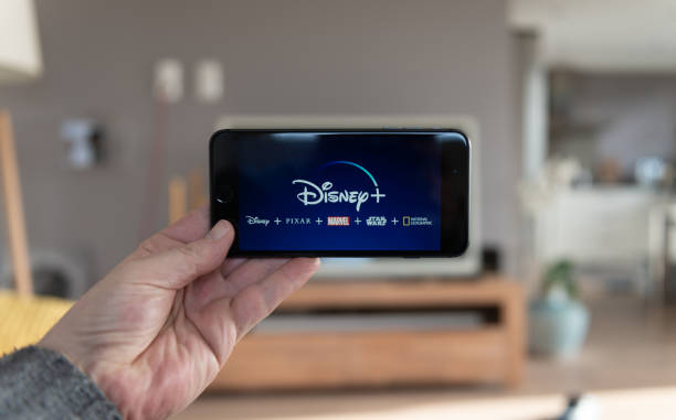 disney+ startscreen on  mobile phone. disney+ online video, content streaming subscription service. man holds his smartphone up and looks at disney plus - serie televisiva foto e immagini stock