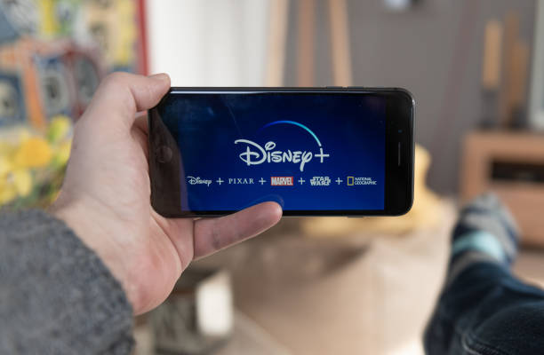 disney+ startscreen on  mobile phone. disney+ online video, content streaming subscription service. disney plus, star wars, marvel, pixar, national geographic. - serie televisiva foto e immagini stock
