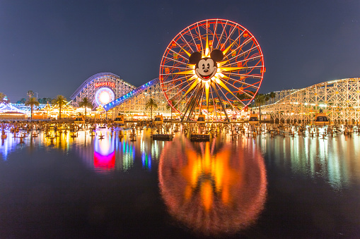 Anaheim, CA USA - August 22, 2015: Disneyland 60th aniversary at Cars Land. This year Disneyland celebrates its 60th aniversary of been open. On this day the park celebrated with fireworks and over 150 thousand people. People walk around rides and games at the downtown Cars Land during the night time..