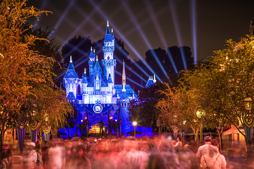 Anaheim, CA USA - September 3, 2015: Disneyland 60th celebration castle with people This year Disneyland celebrates its 60th aniversary of been open. On this day the park celebrated with fireworks and over 150 thousand people. People are exiting the park after a long day of fun and celebrations.