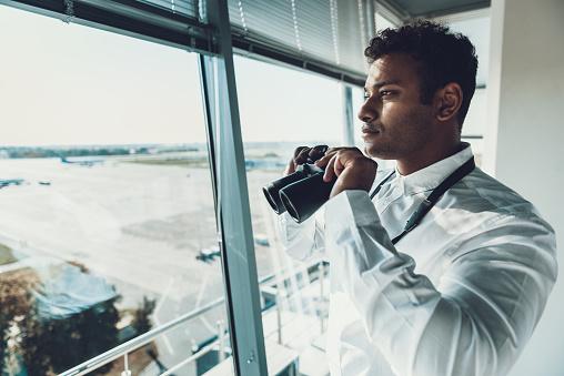 Dispatcher holding binocular in hands on work place