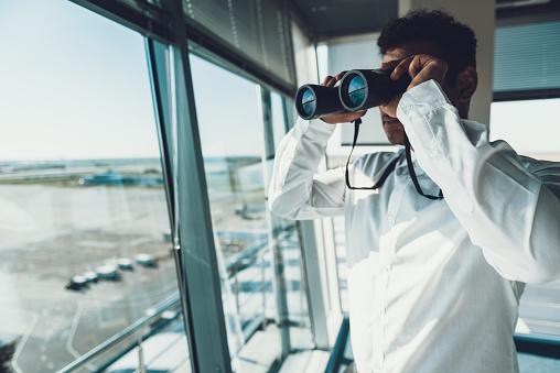 Dispatcher looking at binocular on work place