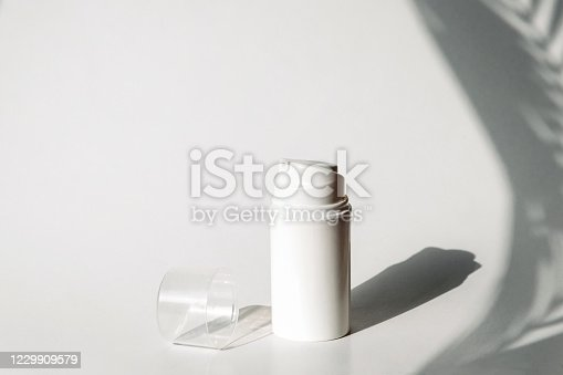 Dispenser for cosmetics products. Skincare and beauty concept. Mockup, copy space. White background with shadows of tropic plants.