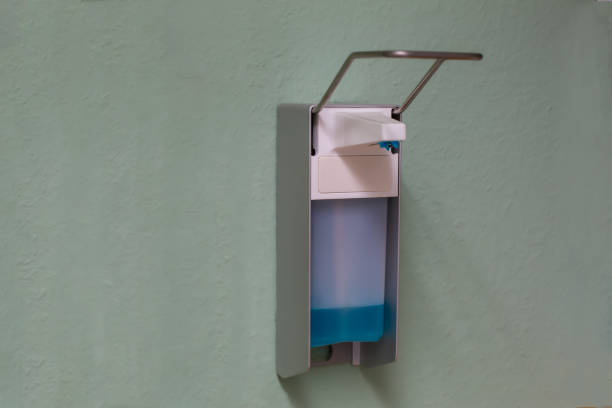 dispenser with a bottle of medical disinfectant hanging on a wall