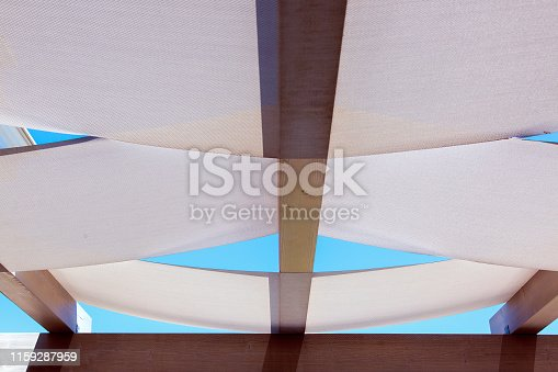 dispersed roof gazebos of textile stretched on wooden roof bars on a sunny day against a blue sky.