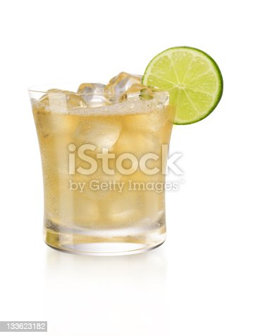 A cold margarita over Ice with a lime garnish, isolated on white